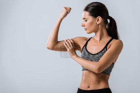Photo pour Attrayant brunette sportive toucher muscle isolé sur gris - image libre de droit