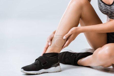 Photo pour Vue partielle du sportif avec douleur à la cheville sur fond gris - image libre de droit