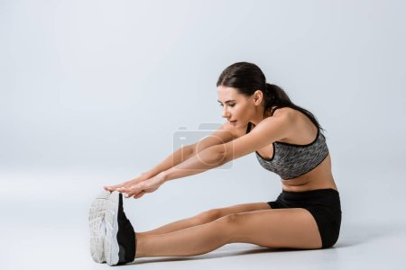 Photo for Attractive brunette sportswoman in sportswear stretching on grey - Royalty Free Image