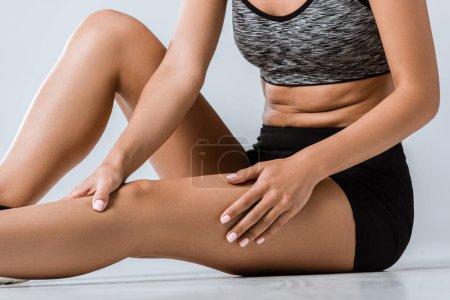 Photo pour Vue recadrée d'une sportive avec douleur aux jambes sur fond gris - image libre de droit