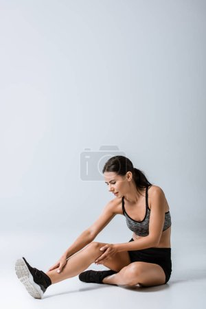 Photo for Attractive brunette sportswoman with leg pain on grey - Royalty Free Image