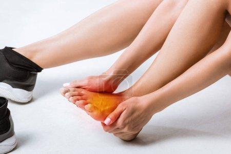 Foto de Vista parcial de la deportista con dolor en el pie en gris - Imagen libre de derechos