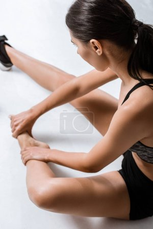 Photo for Overhead view of sportswoman with foot pain on grey - Royalty Free Image