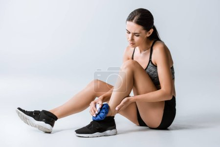 Photo for Sportswoman using ice for leg injury on grey - Royalty Free Image