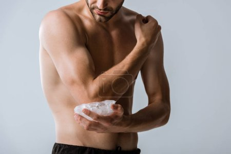 Photo for Cropped view of shirtless sportsman using ice for elbow isolated on grey - Royalty Free Image