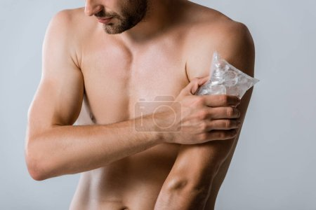 Photo for Cropped view of shirtless man using ice for shoulder isolated on grey - Royalty Free Image
