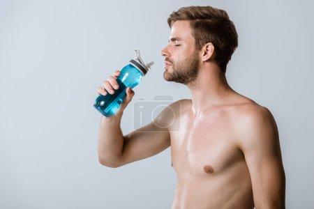 Photo pour Sportif barbu torse nu tenant bouteille de sport isolé sur gris - image libre de droit