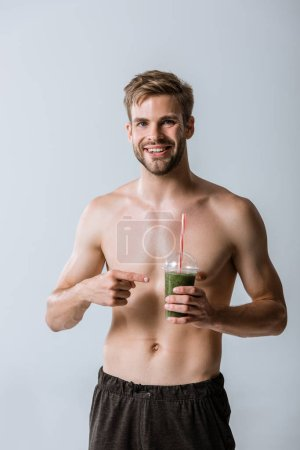 front view of smiling shirtless sportsman pointing with finger at smoothie isolated on grey