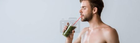 Photo for Panoramic shot of shirtless bearded sportsman drinking smoothie isolated on grey - Royalty Free Image