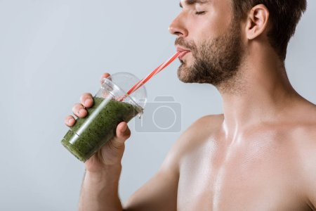 Photo for Shirtless bearded sportsman drinking smoothie isolated on grey - Royalty Free Image