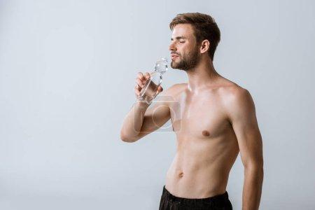 Photo pour L'eau potable de sportif torse nu avec les yeux fermés isolés sur le gris - image libre de droit