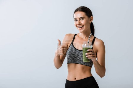 Photo for Smiling sportswoman holding smoothie and showing thumb up isolated on grey - Royalty Free Image