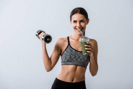 Lächelnde Sportlerin mit Hantel und trinkendem Smoothie isoliert auf grau