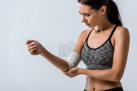 Photo pour Sportive avec bandage élastique sur le coude isolé sur gris - image libre de droit