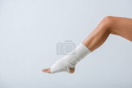 Photo for Partial view of barefoot girl with elastic bandage on foot isolated on grey - Royalty Free Image