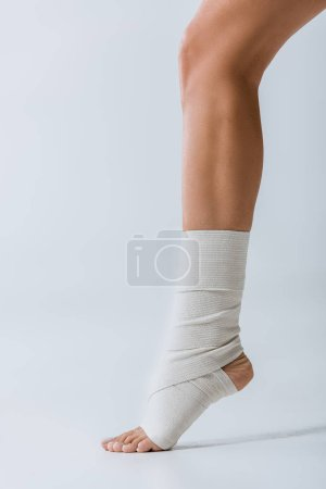 Photo for Partial view of barefoot girl with elastic bandage on foot on grey - Royalty Free Image