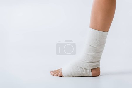Photo pour Vue partielle de la fille nu-pieds avec le bandage élastique sur le pied sur le gris - image libre de droit