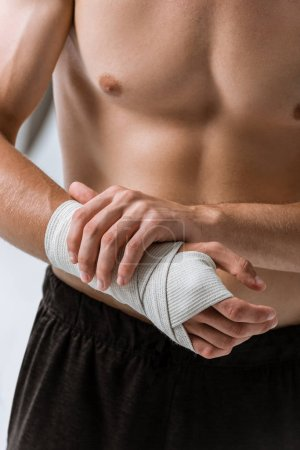 Photo for Cropped view of shirtless sportsman with elastic bandage on wrist isolated on grey - Royalty Free Image