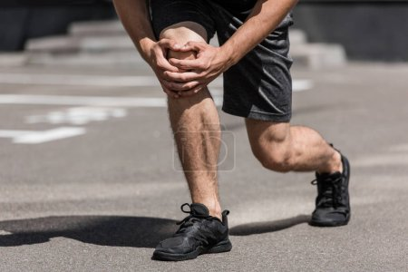 partial view of sportsman with knee pain on street