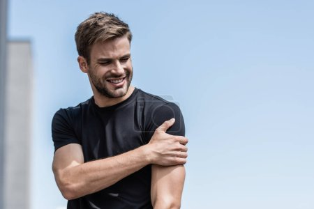 Photo pour Sportif dans le t-shirt noir avec la douleur d'épaule sous le ciel bleu - image libre de droit