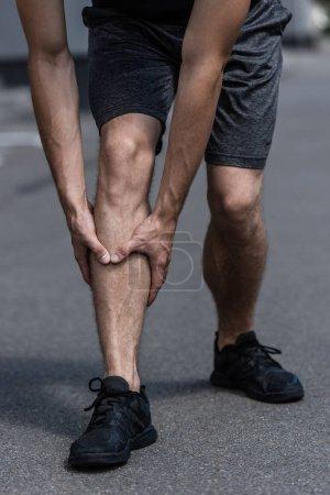 Photo pour Vue partielle du sportif dans des baskets noires avec la douleur de jambe sur la rue - image libre de droit