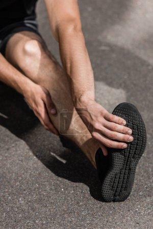 Foto de Vista recortada del deportista con lesión en la pierna en la calle - Imagen libre de derechos