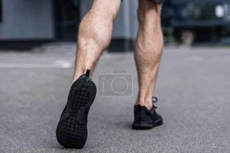 Photo for Partial view of sportsman in black sneakers walking on street - Royalty Free Image
