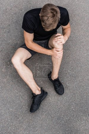 Photo for Overhead view of sportsman with knee pain on street - Royalty Free Image