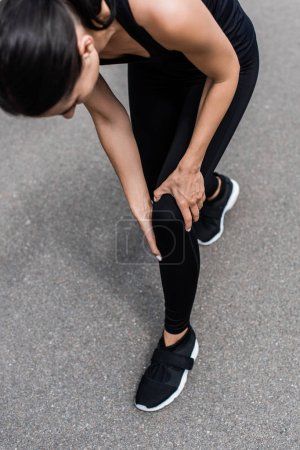 Photo for Cropped view of sportswoman in black sneakers with knee pain on street - Royalty Free Image