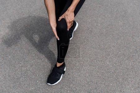 Photo pour Vue recadrée de sportive dans des baskets noires avec la douleur de genou sur la rue - image libre de droit