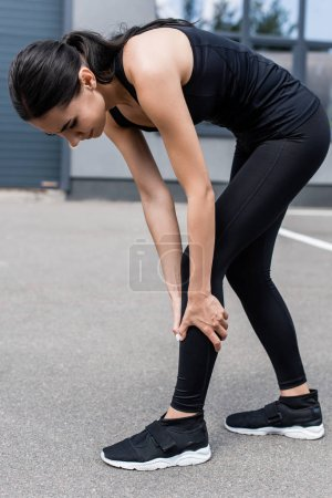 full length view of sportswoman with leg pain on street