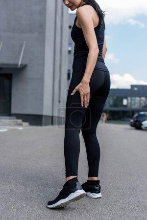 cropped view of sportswoman in black sneakers on street