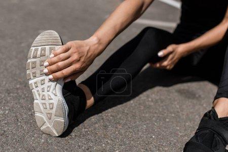 Photo pour Vue partielle de sportive avec la douleur de jambe s'étirant sur la rue - image libre de droit