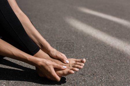 Photo pour Vue partielle du sportif pieds nus avec douleur aux pieds dans la rue - image libre de droit