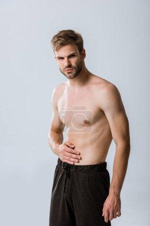 Photo pour Sportif torse nu avec douleur abdominale isolée sur le gris - image libre de droit