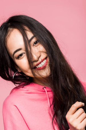Photo pour Attractive asian woman in pink pullover smiling isolated on pink - image libre de droit