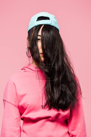 Photo for Attractive asian woman in pink pullover and cap looking at camera isolated on pink - Royalty Free Image