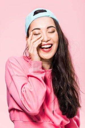 attraktive asiatische Frau mit geschlossenen Augen in rosa Pullover und Mütze lächelt isoliert auf rosa