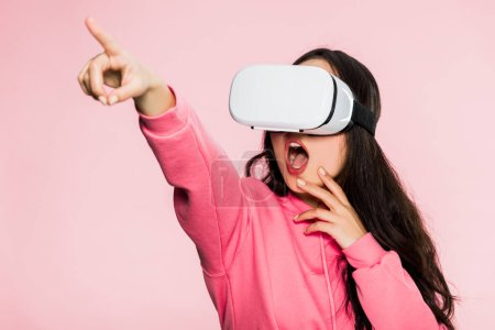 Photo for Shocked woman in pink pullover with virtual reality headset pointing with finger isolated on pink - Royalty Free Image