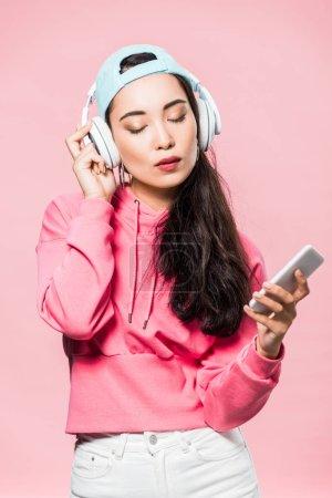 attraktive asiatische Frau in Pullover und Mütze hört Musik und hält ihr Smartphone isoliert auf rosa