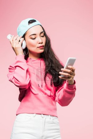 Photo pour Attractive asian woman in pullover and cap listening music and holding smartphone isolated on pink - image libre de droit