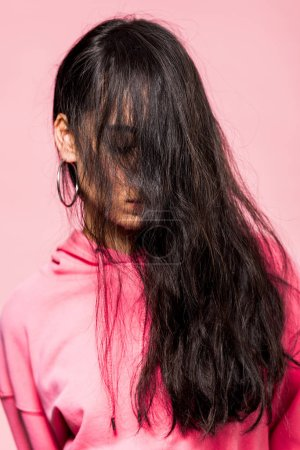 Photo pour Attractive asian woman in pink pullover with closed eyes isolated on pink - image libre de droit