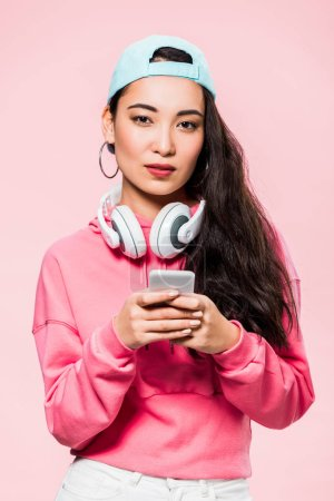 Photo for Attractive asian woman in pullover and cap with headphones holding smartphone isolated on pink - Royalty Free Image