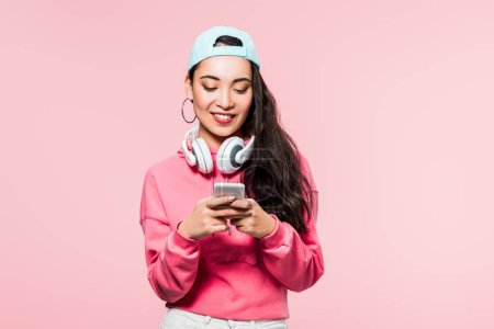 Photo for Smiling asian woman in pullover and cap with headphones holding smartphone isolated on pink - Royalty Free Image