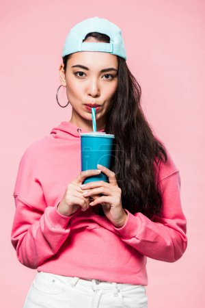 Photo for Attractive asian woman in pullover and cap drinking from plastic cup isolated on pink - Royalty Free Image