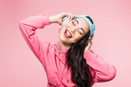Photo pour Attractive asian woman in pullover and cap listening music and smiling isolated on pink - image libre de droit