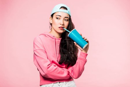 pensive asian woman in pullover and cap drinking from plastic cup isolated on pink