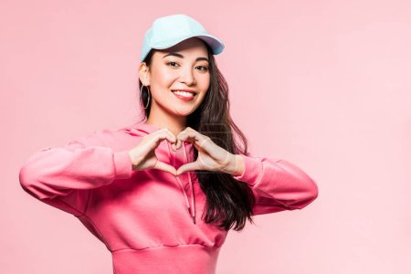 Photo pour Attractive asian woman in pink pullover and cap smiling and showing heart symbol isolated on pink - image libre de droit