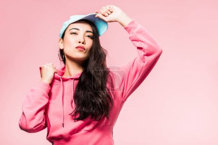 Photo pour Attractive and pensive asian woman in pink pullover and cap looking away isolated on pink - image libre de droit