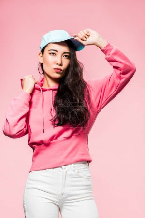 Photo for Attractive and pensive asian woman in pink pullover and cap looking away isolated on pink - Royalty Free Image